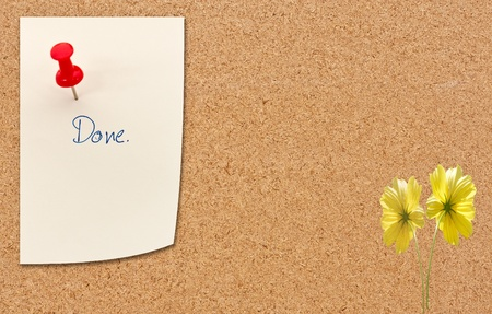 ersatz: push pin with paper note with done wording on cork billboard and flowers
