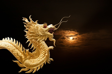 golden dragon statue with column and sunset background