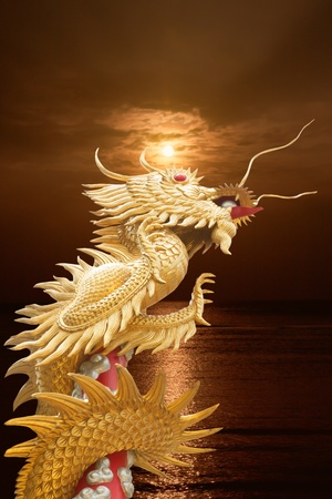 golden dragon statue with column and sunset background photo