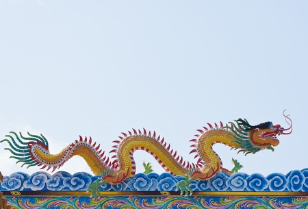 golden Chinese Dragon  on roof  with blue sky background. photo