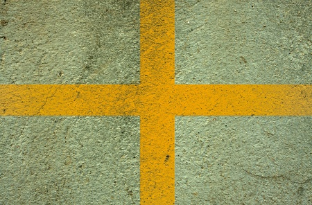 yellow  cross on cement wall background photo
