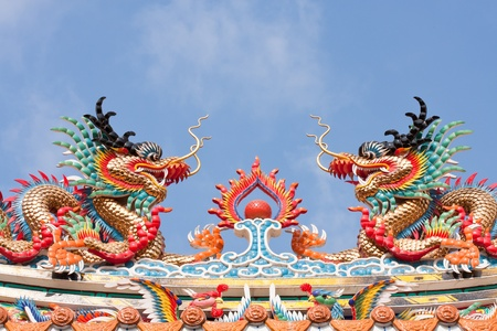 twin dragon statues in Chinese style on top of general temple roof  against blue sky