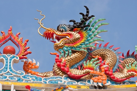 dragon statues in Chinese style on top of general temple roof  against blue sky photo