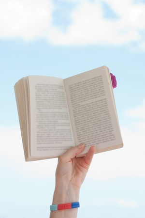 Hand holding book over blue sky photo