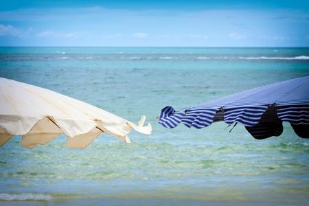 blue Beach umbrella on a sunny day, sea in background photo