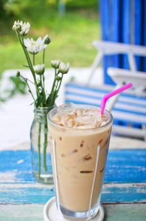 ice coffee on grunge wood table in garden photo