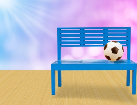 soccer ball,blue chair on yellow wood floor and abstract light background photo
