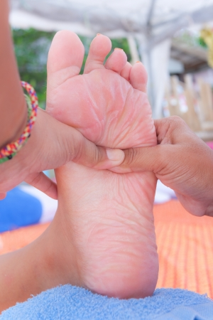Foot massage is a type of massage in Thai style that involves stretching and deep massage  Stock Photo