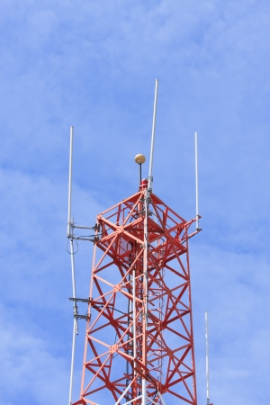 Telecommunications tower against blue sky background photo