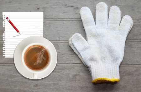White work gloves,paper and coffee lying on wood floor photo