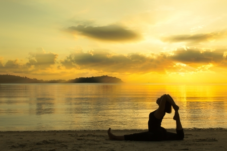 silhouette of a beautiful yoga girl at sunrise on the beach Stock Photo