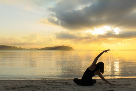 silhouette of a beautiful yoga girl at sunrise on the beach photo