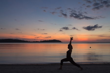 Silhouette of a beautiful yoga girl at sunrise on the beach,High Lunge pose photo