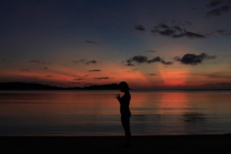 yogini: Silhouette of a beautiful yoga girl at sunrise on the beach,Upward Salute Pose Stock Photo
