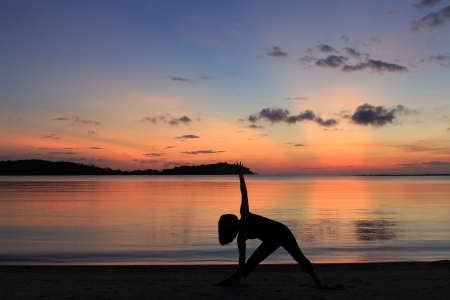 Silhouette of a beautiful yoga girl at sunrise on the beach,Extended Triangle Pose photo