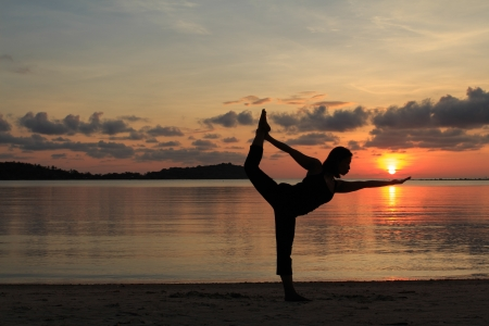 Silhouette of a beautiful yoga girl at sunrise on the beach,Natarajasana,Lord of the Dance Pose photo