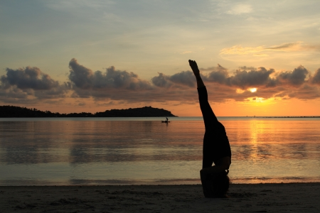 Silhouette of a beautiful yoga girl at sunrise on the beach,Urdhva Prasarita Eka Padasana,Standing Split pose photo