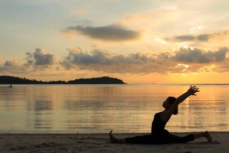 Silhouette d'une jeune fille belle yoga au lever du soleil sur la plage,, Hanumanasana, Monkey Pose