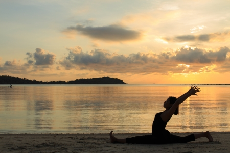 Silhouette of a beautiful yoga girl at sunrise on the beach,,Hanumanasana,Monkey Pose Stock Photo