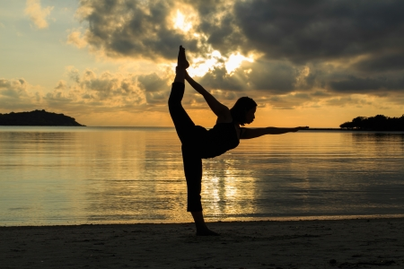 yogini: Silhouette of a beautiful yoga girl at sunrise on the beach