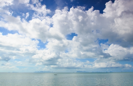 Panoramic seascape with puffy white clouds,blue sky and green ocean photo