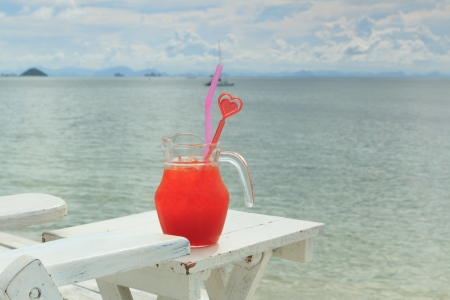 Red cocktail on white table set over ocean photo