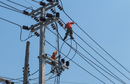 An electrical power utility worker fixes the power line  photo