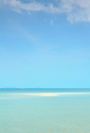 Seascape with puffy white clouds,sand and blue sky photo