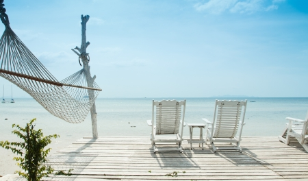 white beach chair  and hammock facing ocean photo