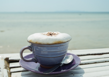 cup of hot coffee with sea background photo