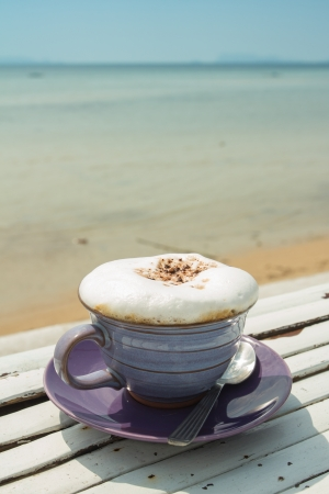 cup of hot coffee with sea background