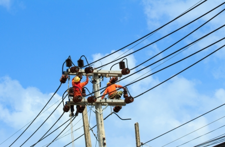 An electrical power utility worker fixes the power line