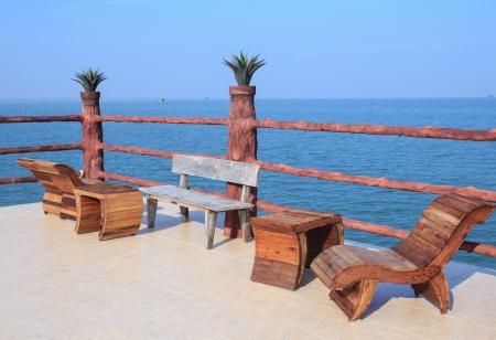 chaises en bois sur une terrasse sur l'oc�an