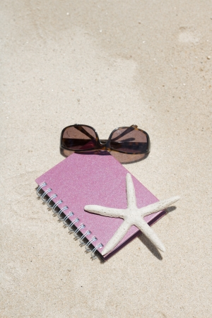 Notebook sunglass and starfish lying on beach photo