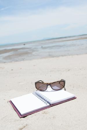 Notebook sunglass and starfish lying on beach photo