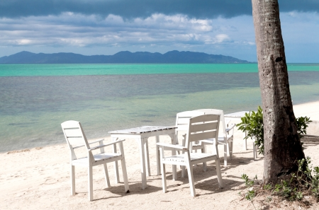 White table set on sand beach facing the ocean photo