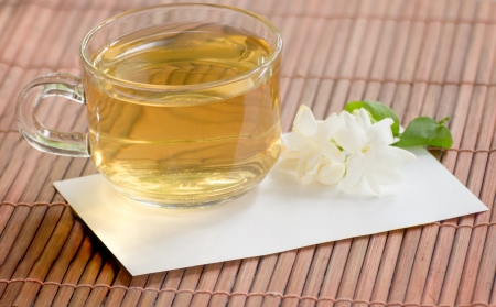 Cup of jasmine tea and flower on bamboo mat photo