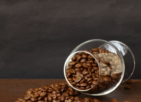 Coffee beans in wineglass on wooden board photo