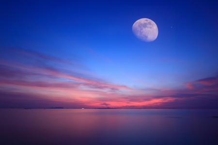 Chiaro di luna sopra il mare azzurro e cielo fuoco, tecnica di lunga esposizione
