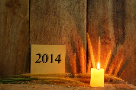 Still life with 2014 wrote on notepad and candle light on wooden background photo