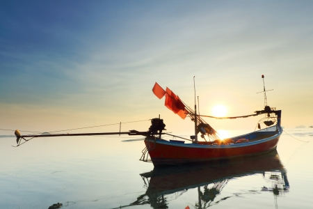 long tailed boat: Long tail boat in the sunrise over sea and blue sky  Stock Photo