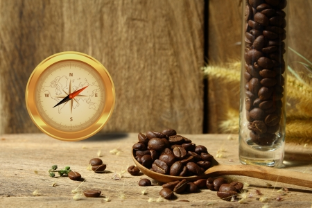 Still life compass with roasted coffee beans in glass vase  on wooden background photo