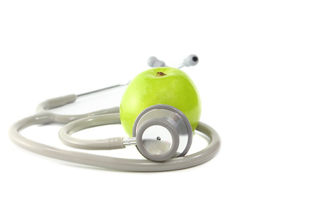 Stethoscope and green apple on white background,diet for good life concept photo