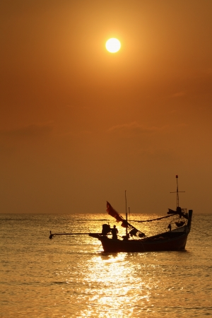 Stunning golden sunset over sea and sky with fishing boat floating photo