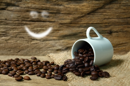 Roasted coffee beans  and smile symbol on grunge wooden  background photo