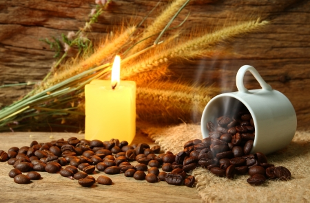 Still life roasted coffee beans and candle burened with foxtail weed on wooden background photo