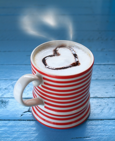 Red coffee cup with heart latte art on blue wooden board  photo