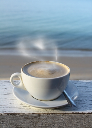 Coffee cup in morning on grunge terrace facing seascape  photo