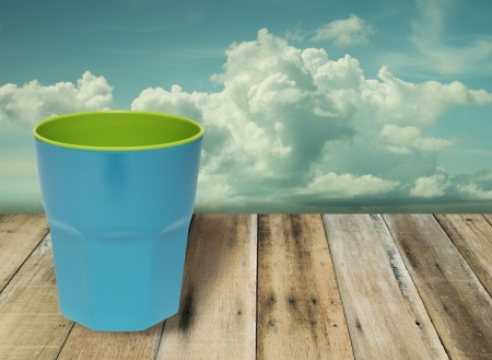 Blue cup on grunge wood floor with blue sky white cloud in vintage style  photo