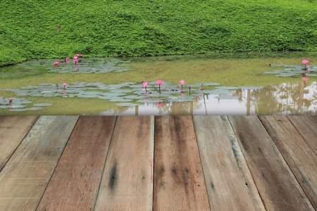 Grunge wooden terrace and water lily on pond outdoor photo